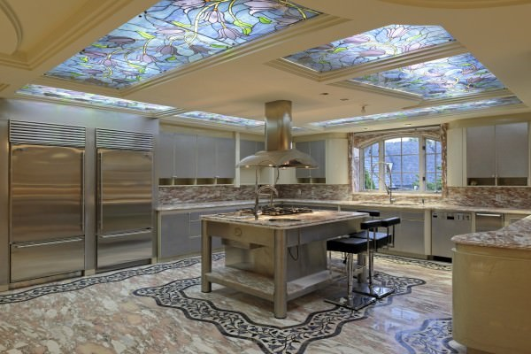 the-kitchen-sits-under-stained-glass-skylights-it-has-plenty-of-custom-touches-like-stone-flooring-two-steel-refrigerators-and-a-center-island-mounted-range-and-hood