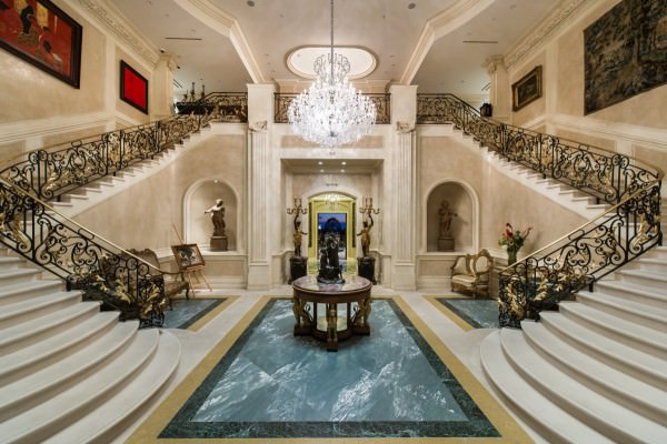 visitors-pass-through-three-sets-of-gates-before-arriving-at-the-grand-home-the-two-story-entry-has-a-pair-of-curved-marble-staircases