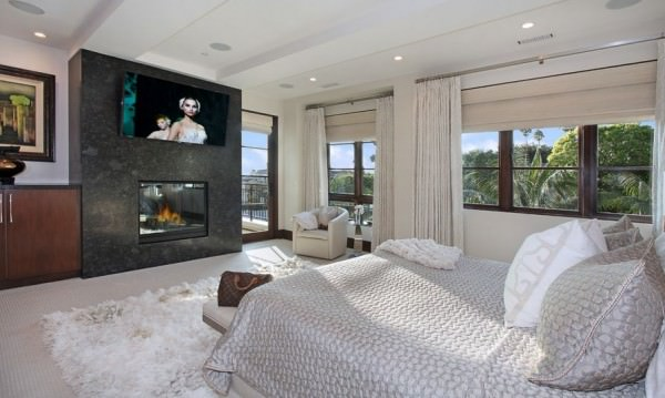 Modern-bedroom-with-fireplace-and-tv-above