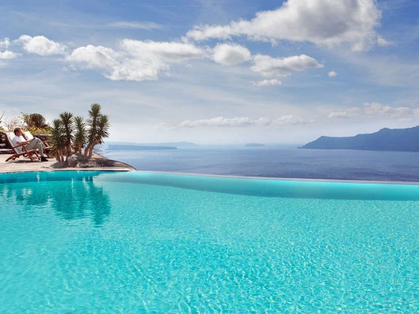 the-perivolas-hotel-in-greece-has-the-one-of-the-most-beautiful-infinity-pools-with-blue-water-that-seems-to-spill-out-right-into-the-mediterranean